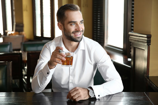 Young man with glass of whiskey and cigar in pub