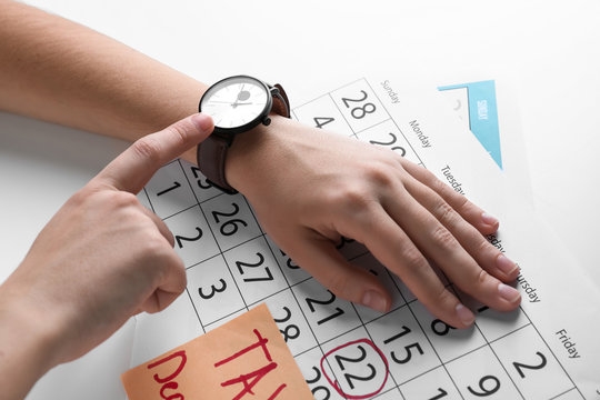Woman looking at her watch and calendar on light table. Deadline concept