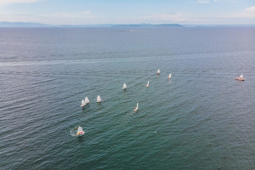 Aerial drone photo of young teenagers on small sailing boats competing in the regatta at mediterranean emerald sea