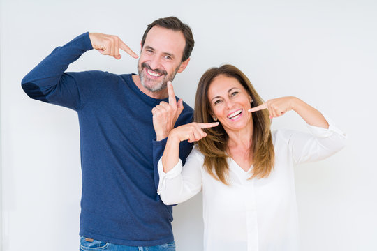 Beautiful middle age couple in love over isolated background smiling confident showing and pointing with fingers teeth and mouth. Health concept.