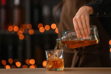Female bartender pouring whiskey from bottle into glass on table Fototapete