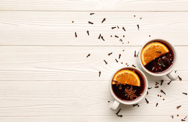 Cups of tasty mulled wine on white wooden background