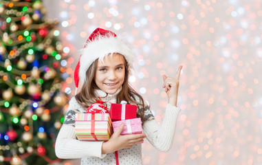 Happy little girl holding many gift boxes and pointing away. Empty space for text