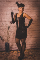 a girl with short black hair with a bandage with sequins and feathers on her head in a dress with sequins in the Chicago style of 20 years, with a cigar in the style of gangsters, against a brick wall