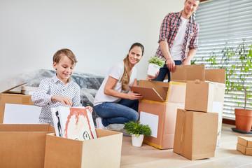 Familie packt Umzugskartons aus beim Umzug