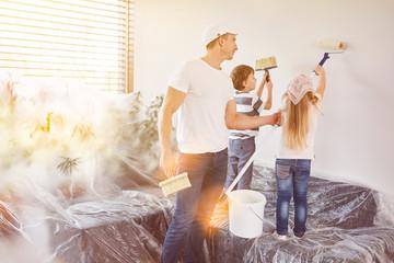 Kinder helfen Vater beim Wand streichen in Haus