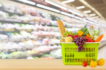 Shopping basket filled with fruits and vegetables on wood table with supermarket grocery store blurred defocused background