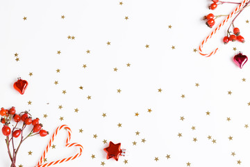 Christmas composition. Red rosehip berries, Christmas candy cane on a white background and golden stars. Christmas, new year, winter concept. Flat lay, top view, copy space