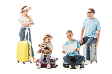 Family sitting on luggage and looking at map isolated on white