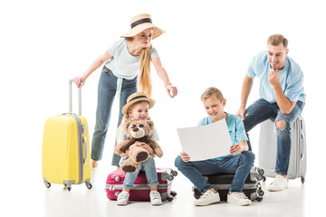 Mother pointing at map and kids with dad sitting on luggage isolated on white