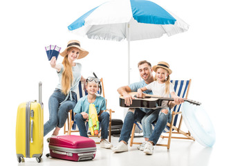 Happy family sitting on deck chairs with guitar and passports isolated on white