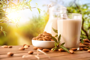 Almond drink on table with jug in the field closeup