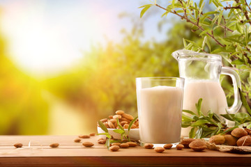 Almond drink on wooden table with jug in the field