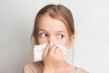 Runny nose in children. A child blows his nose in a handkerchief