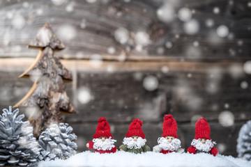 Vier Weihnachtsmänner im Schnee warten auf den Advent