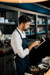 Barman standing in apron with digital tablet in bar