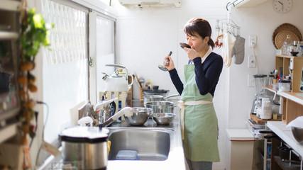 調理の味見をする主婦