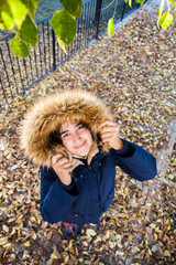 Beautiful teen poses with her coat among the autumn leaves in a sunny afternoon