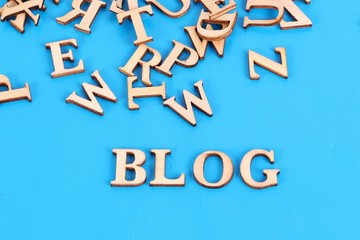 a heap of wooden letters are lying in the blue studio with the word blog in the front