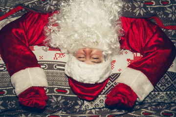 Authentic Santa Claus is lying in bed at home.