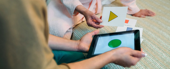 Female doctor showing geometric shape game to elderly female patient with dementia Wall mural