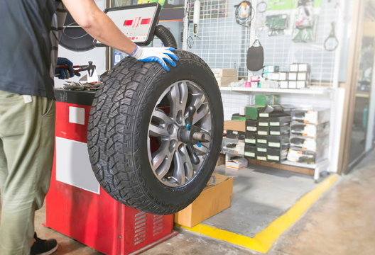 Mechanic balancing a car wheel on an automated machine at the garage.