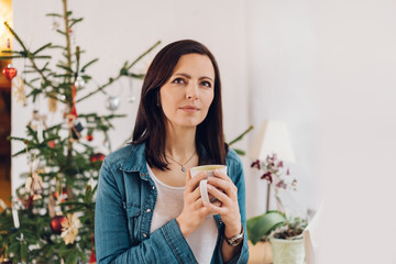 Woman holding cup of tea against Christmas tree