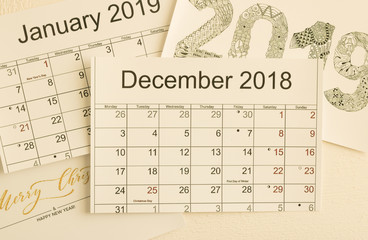 Close-up: calendar December 2018 is on top of images of calendar January 2019 and holiday greetings. Top view. Concept: Merry Christmas and Happy New Year holidays.