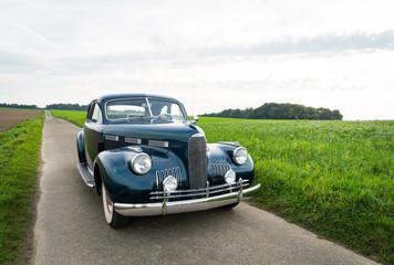 Oldtimer Cadillac Lasalle Coupe 1940 auf einer Landstraße Wall mural