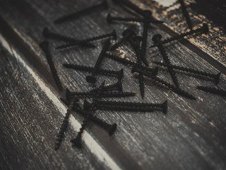 Nails and anchors scattered on the dark wooden table in a rustic style