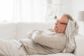 old age, problem and people concept - thoughtful senior man lying on sofa at home