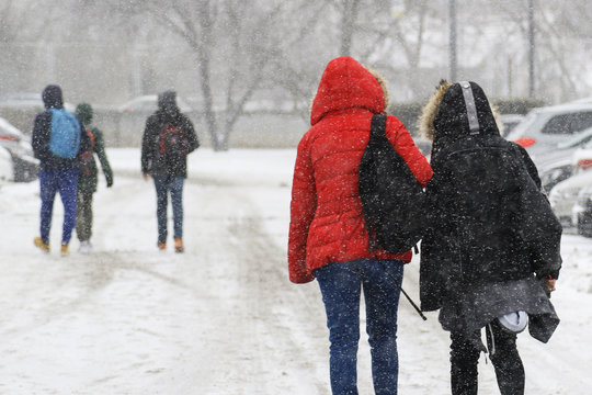 teenagers going from school on heavy snow