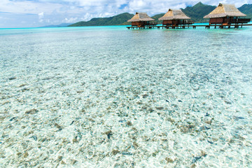 travel, tourism, vacation and summer holidays concept - bungalow huts in sea on tropical resort beach in french polynesia