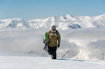Manful snowboarder walking in the mountain resort