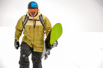Man walking with the black and green snowboard in the mountain resort