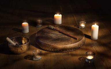 Shaman tambourine and Tibetan bowl surrounded by candles in a dark room.