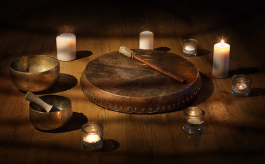 Shaman tambourine and Tibetan bowl with candles in a dark room.