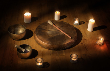 The set of Shaman tambourine, Tibetan bowl and candles in a dark room.