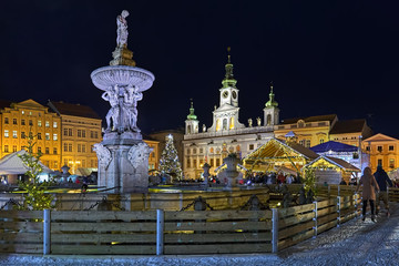 Ceske Budejovice, Czech Republic. Christmas market at the Premysl Otakar II Square with ice-skate rink around the Samson fountain in night. The Town Hall is visible in the background.