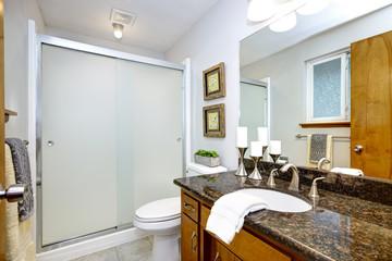 Remodeled bathroom with dark granite counter top vanity