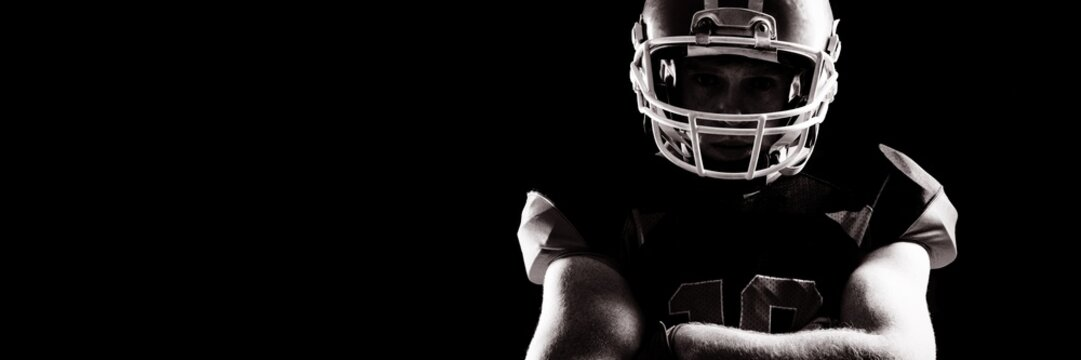 American football player in helmet standing with arms crossed