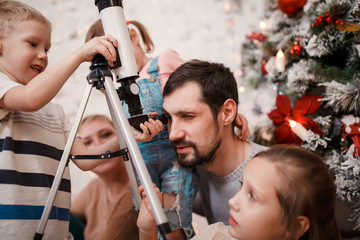 Parents and daughters,son with telescope on background of decorated New Year's fir
