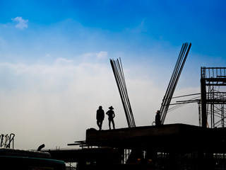 Construction team working at site, silhouette of construction worker.