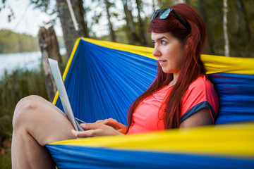 Photo of brunette with laptop sitting in hammock