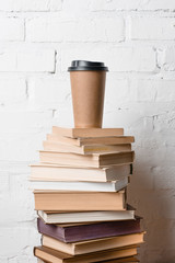 coffee to go on pile of books near white brick wall