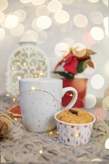Winter still life from scarf, white mug of cocoa, coffee or hot chocolate, muffin, christmas tree on warm plaid with garland.