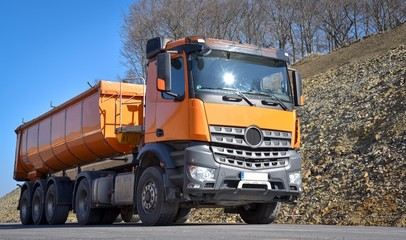 Oranger Lastkraftwagen auf einer Straßenbaustelle