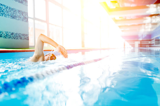 Photo of athlete man from side swimming in pool at workout.