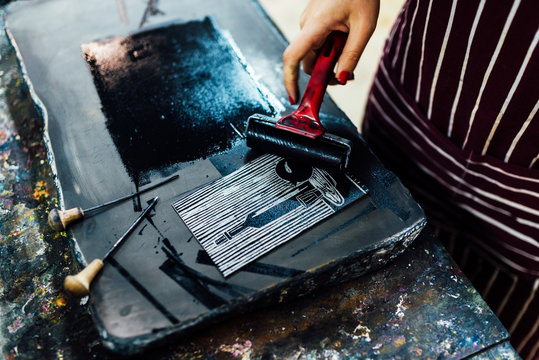 linocut. rolling paint on a piece of linoleum