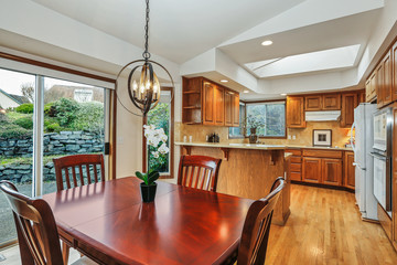 Kitchen interior with cherry wood dining room table and orange tone cabinets in large room.